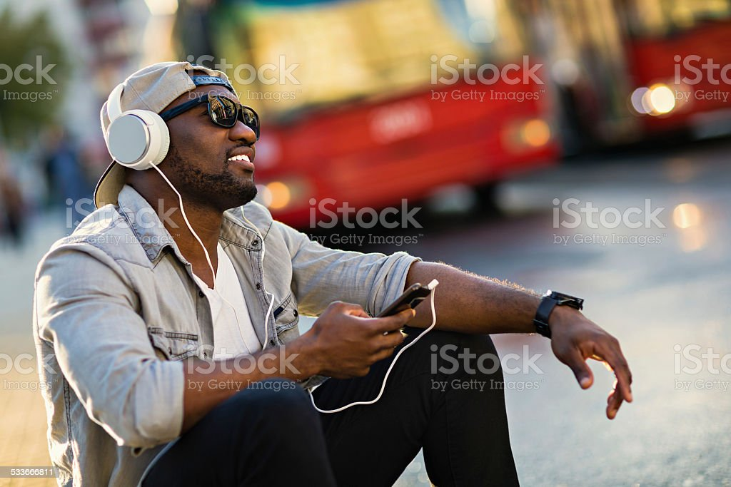 Young man listening to music on mobile phone stock photo
