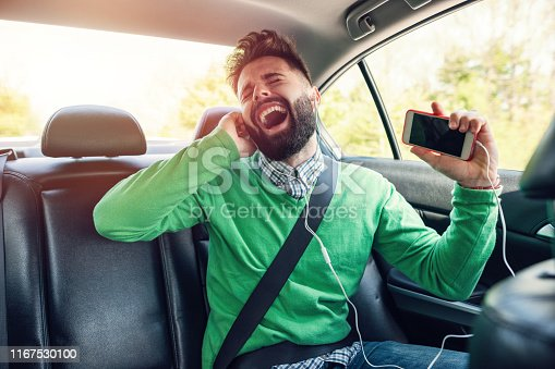Excited young man listening to music and singing loud in the car
