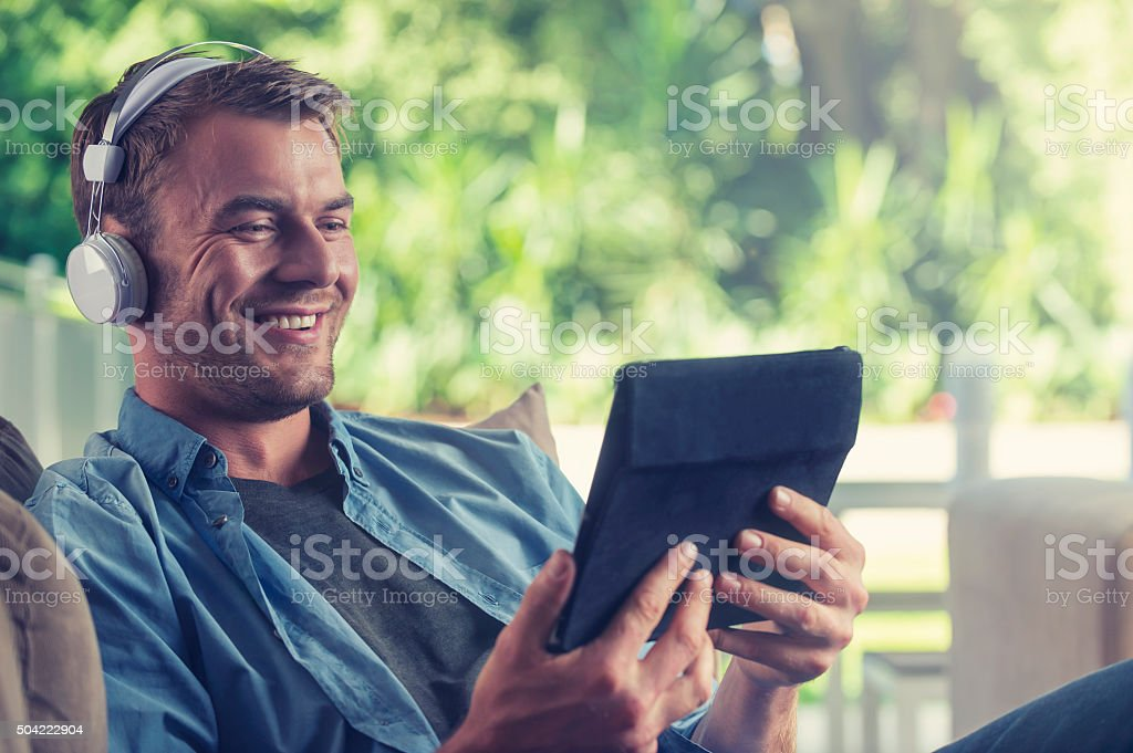 Young man listening to music with a digital tablet stock photo