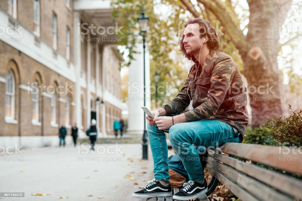 Handsome young man listening to favorite radio station podcast on his...