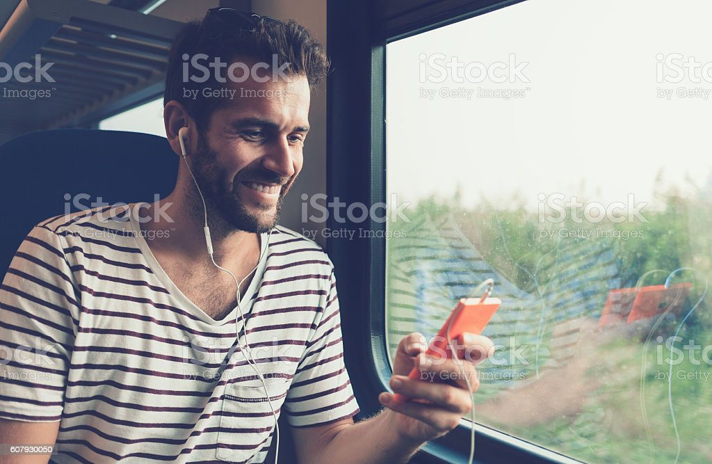 Young man listening to the music on the train stock photo