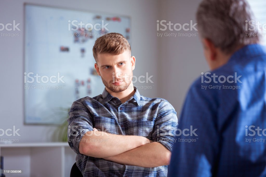 Young man listening to therapist in lecture hall Young student with arms crossed listening to mental health professional. Therapist is discussing with man. They are in lecture hall at university. 20-24 Years Stock Photo