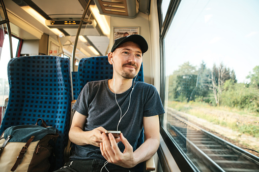 A young man listens to a music or podcast and looks out the window while the train is moving.