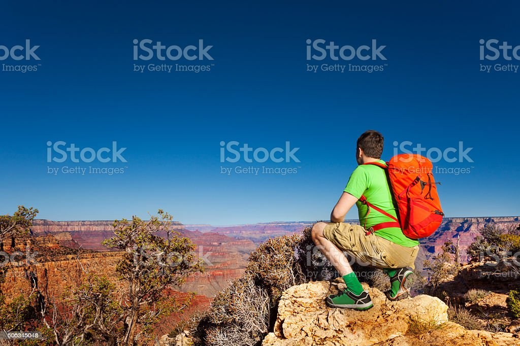 Young man look at grand Canyon sit on squads stock photo
