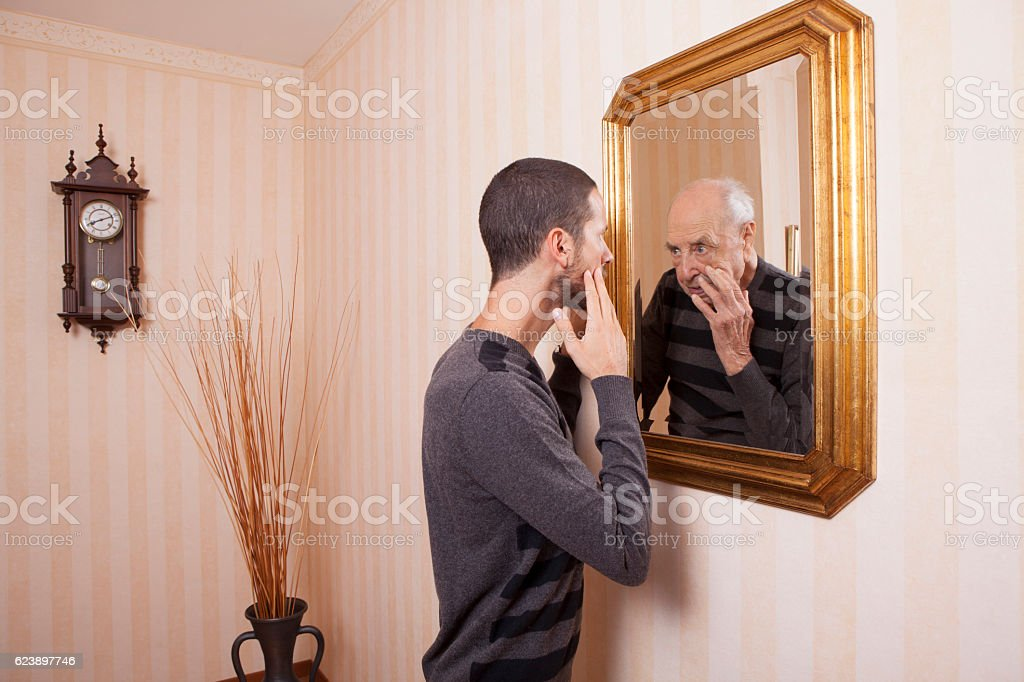 young man looking at an older himself in the mirror stock photo