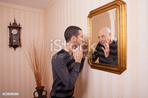 661896674istockphoto young man looking at an older himself in the mirror 623898086