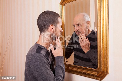 661896674istockphoto young man looking at an older himself in the mirror 623898434