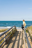 Young man sitting on boardwalk looking at  waves on a sunny day, Atlantic Ocean horizon.