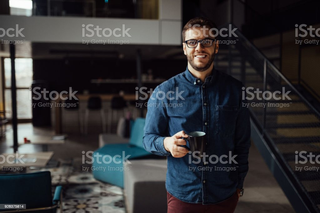 Junger Mann, Blick auf Kamera stehend im modernen Büro – Foto