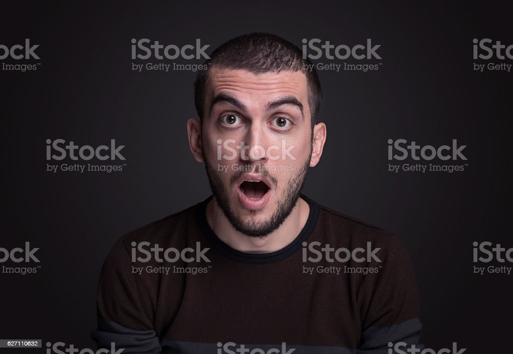 Young man looking at camera with a shock expression stock photo