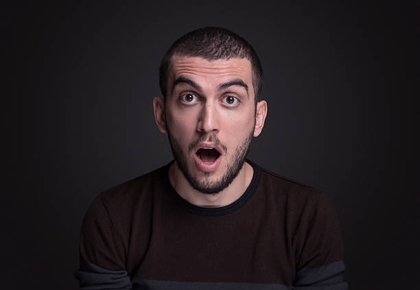 Young man looking at camera with a shock expression Young man looking at camera with a shock expression  over gray background,studio shot mouth open stock pictures, royalty-free photos & images