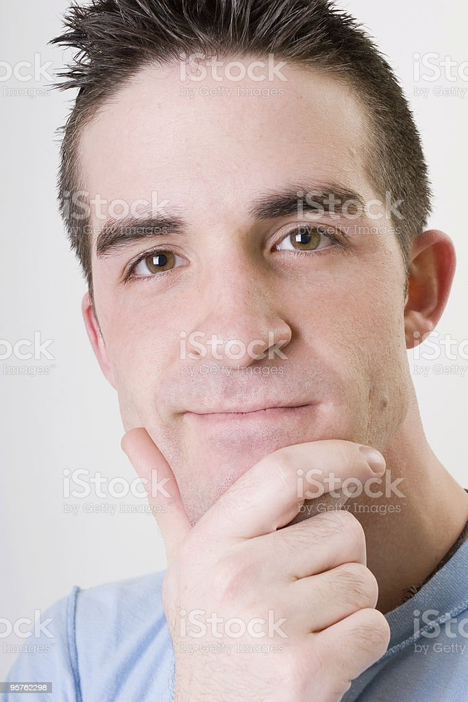 Young Man looking at Camera with his Hand on Chin stock photo