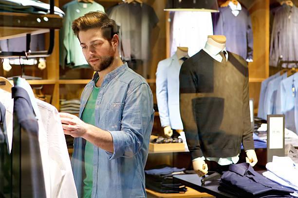 junger mann, blick auf kleidung zu kaufen sie im shop - herren outfit stock-fotos und bilder