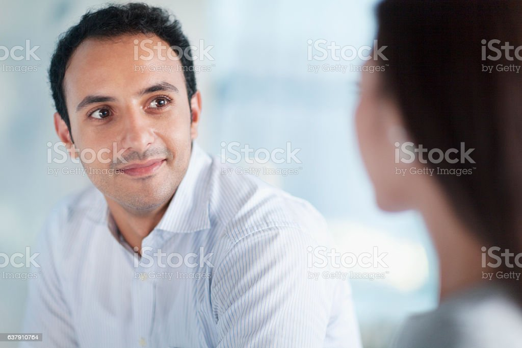 Young man looking at colleague in office​​​ foto