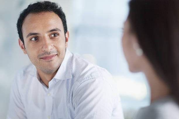 Young man looking at colleague in office stock photo
