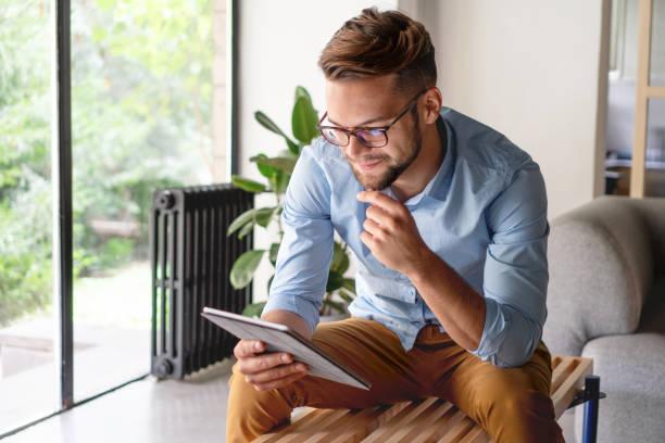 Young Man looking at digital tablet Young Man looking at digital tablet ipad stock pictures, royalty-free photos & images