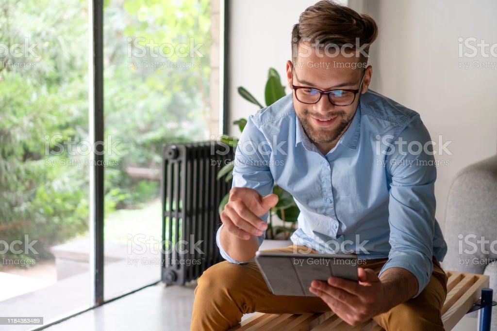 Young Man looking at digital tablet Young Man looking at digital tablet Adult Stock Photo