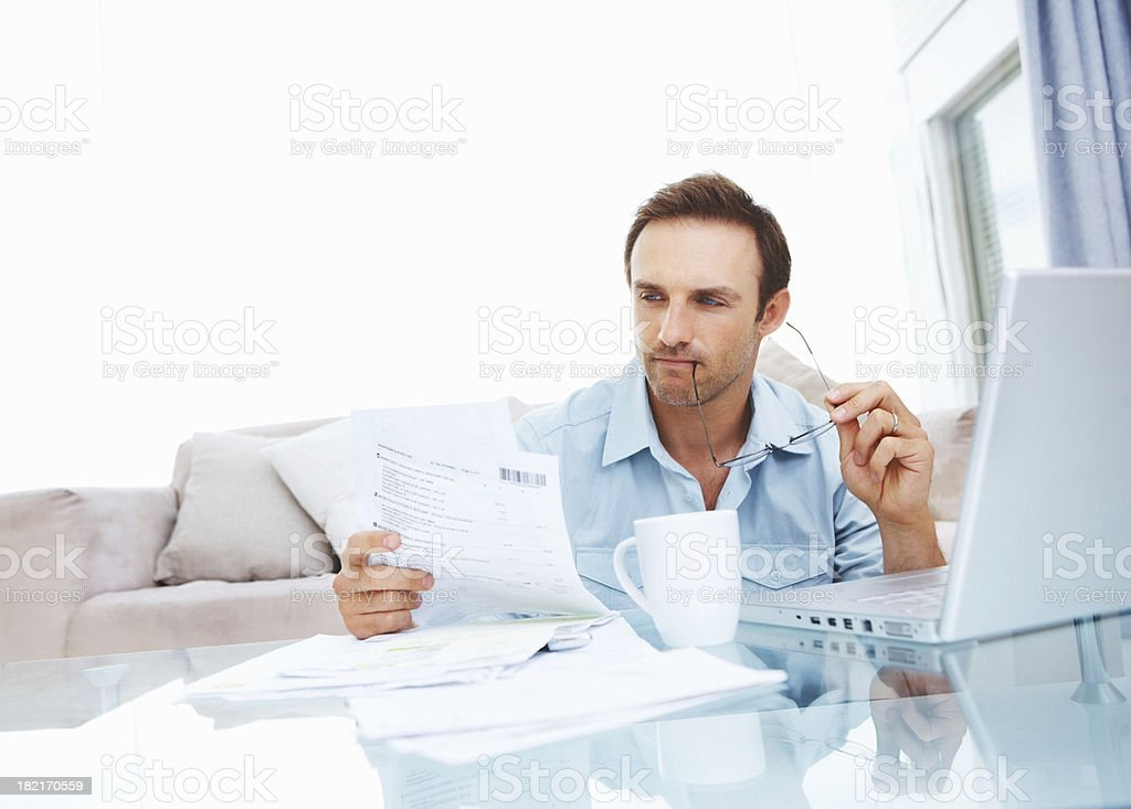 Young man looking at documents by laptop royalty-free stock photo