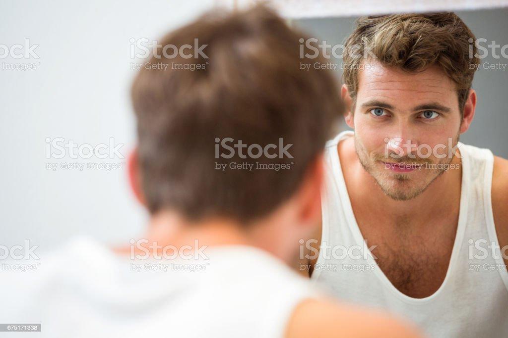 Junger Mann sich selbst im Spiegel betrachten – Foto