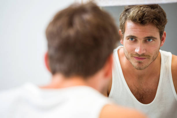 Young man looking at himself in mirror stock photo