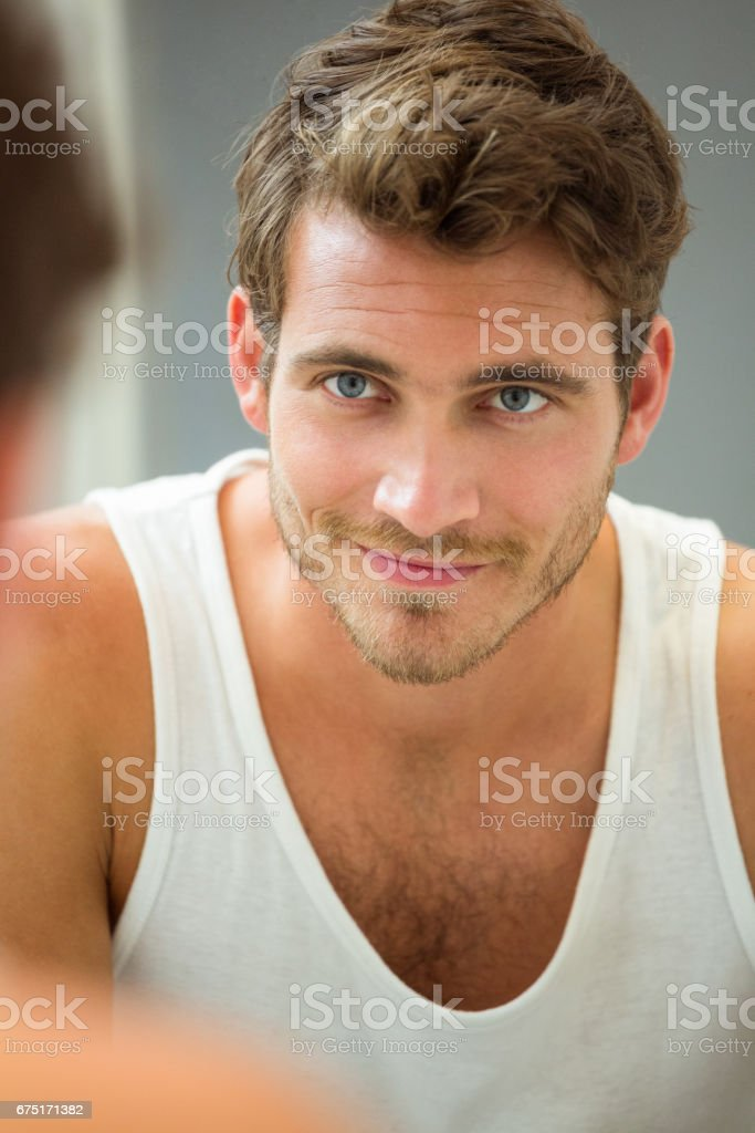 Young man looking at himself in mirror - foto stock