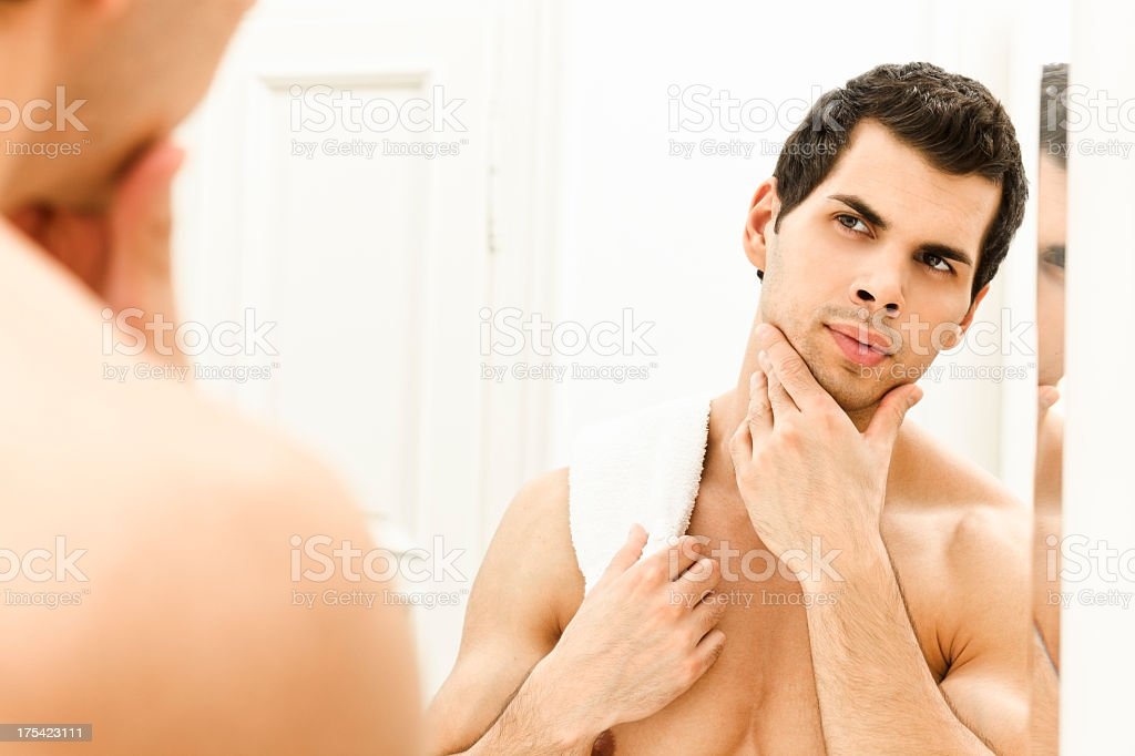 Young man looking at his face in mirror royalty-free stock photo