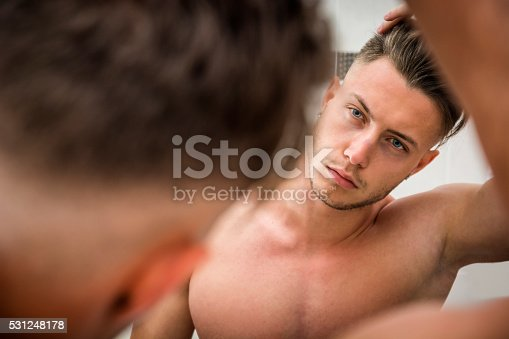 istock Young man looking at his hair in bathroom mirror 531248178