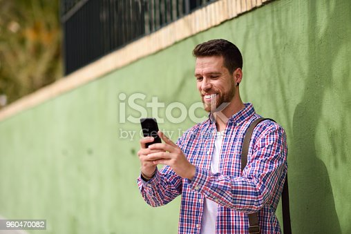 Young man looking at his smart phone and smiling in urban background. Guy wearing casual clothes. Lifestyle concept.