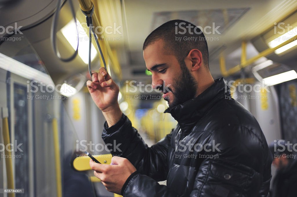 Young man looking at his smartphone in train royalty-free stock photo
