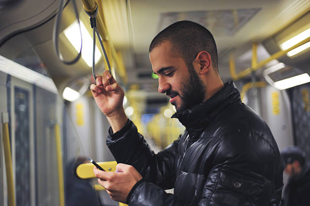 Young man looking at his smartphone in train stock photo