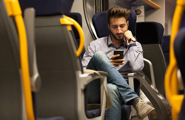 junger mann, blick auf seinem smartphone im zug - marko skrbic stock-fotos und bilder