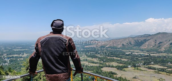 Srinagar, Jmamu and kashmir - A young man looking at mountains and green landscape from a top of a mountain.