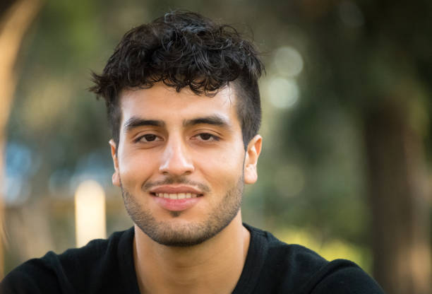 Young man looking at the camera Young man looking at the camera at the park smiling armenian ethnicity stock pictures, royalty-free photos & images