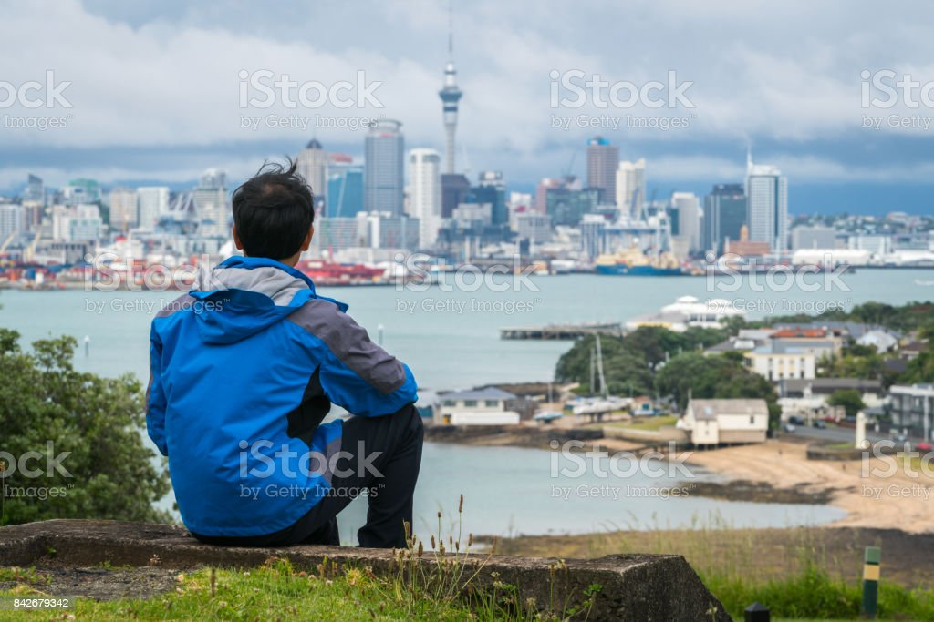 Young man looking Auckland city skyline stock photo