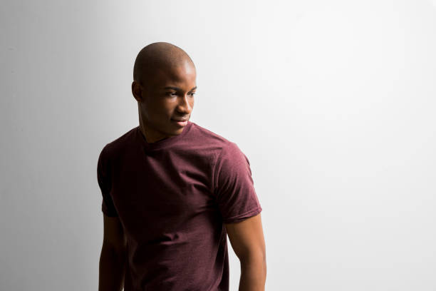 Young man looking away against white background Young man standing against white background. Completely bald male is wearing maroon t-shirt. He is looking away. shaved head stock pictures, royalty-free photos & images
