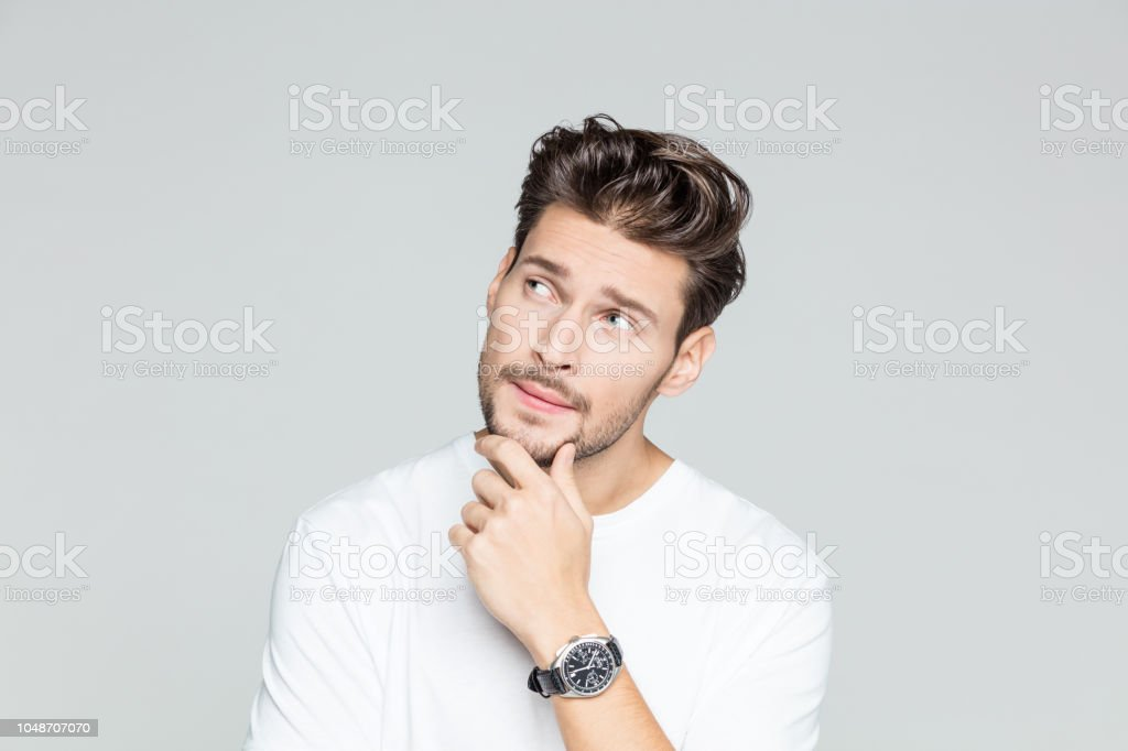 Young man looking away and thinking Portrait of handsome young man looking away and thinking on grey background 25-29 Years Stock Photo
