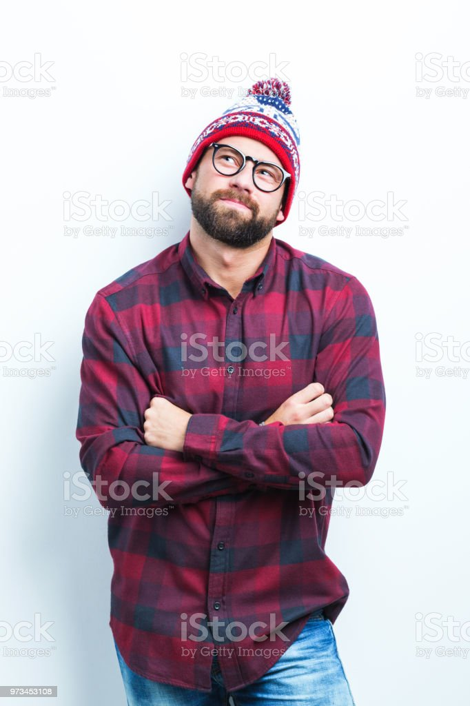 Young man looking away Portrait of handsome young man in winter cap standing with his arms crossed and looking away on white background Adult Stock Photo