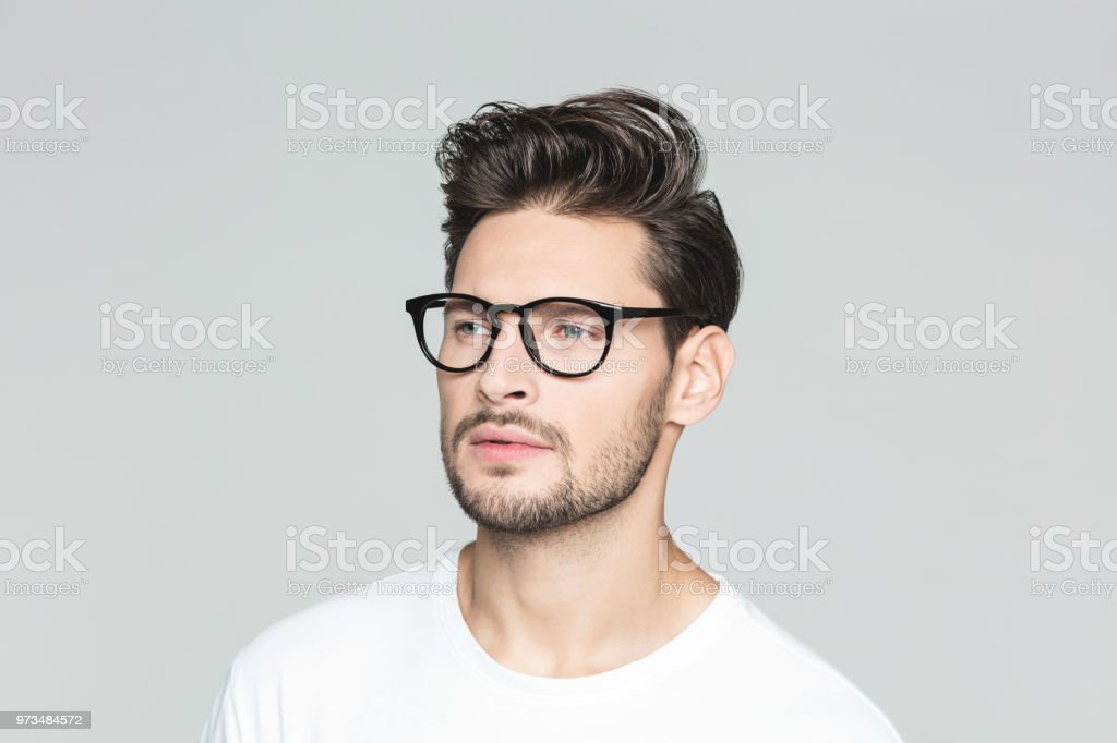 Young man looking away Close up of young man wearing glasses looking away on grey background 25-29 Years Stock Photo