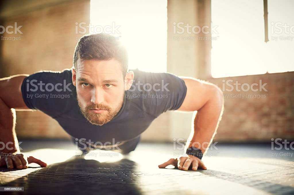 Young man looking away while doing push-ups in gym stock photo
