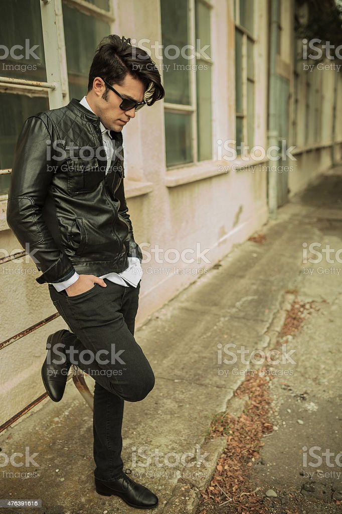 young man looking down while leaning on a ladder stock photo
