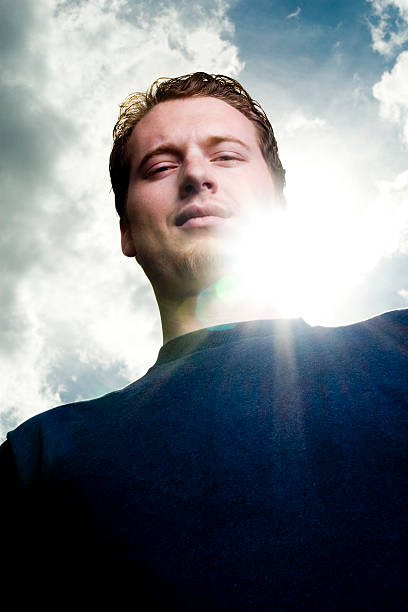 Young Man Looking Down with Sunlight Behind Him stock photo