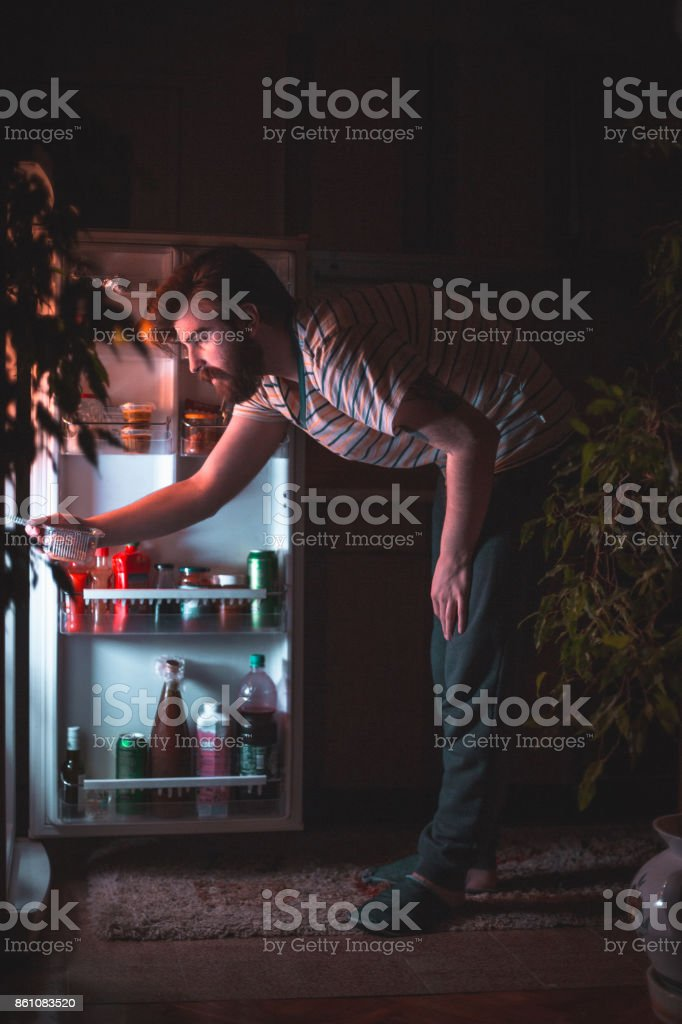 Young man looking for what to eat late night stock photo