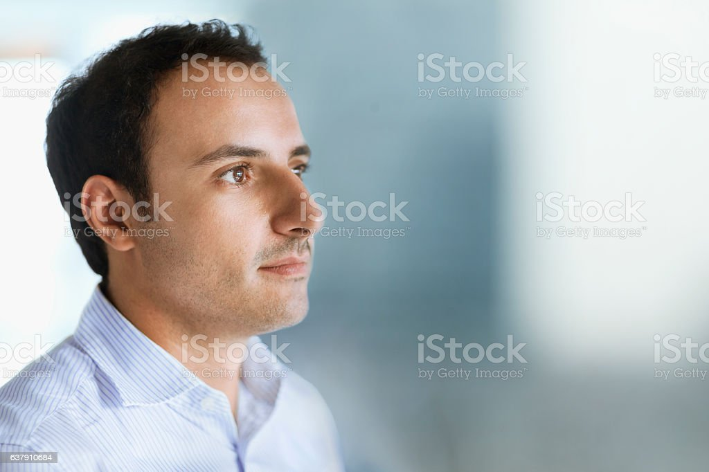 Young man looking forward in office space stock photo