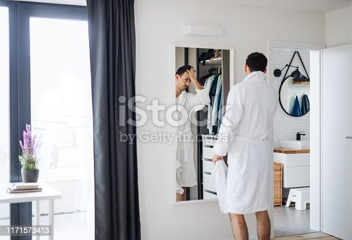 A young man looking in mirror in bedroom in the morning, daily routine.