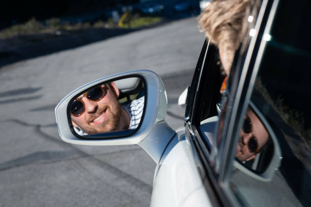 young man looking in the side view mirror of his car - pila a idrogeno foto e immagini stock