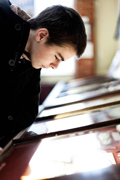 junger mann, ein blick in eine präsentation hinter glas - vitrinenschrank stock-fotos und bilder