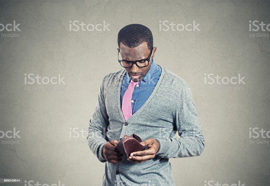 Young man looking into his empty wallet has no money stock photo