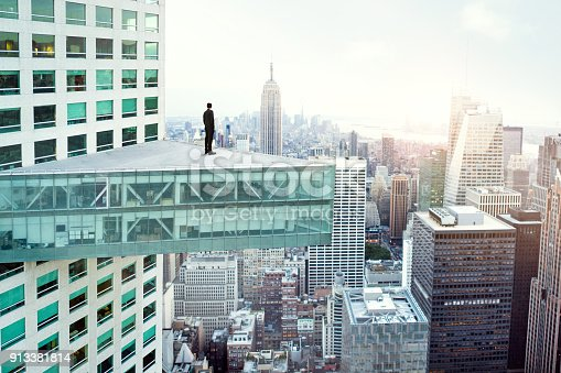 istock Young man looking out at city skyline in New York 913381814