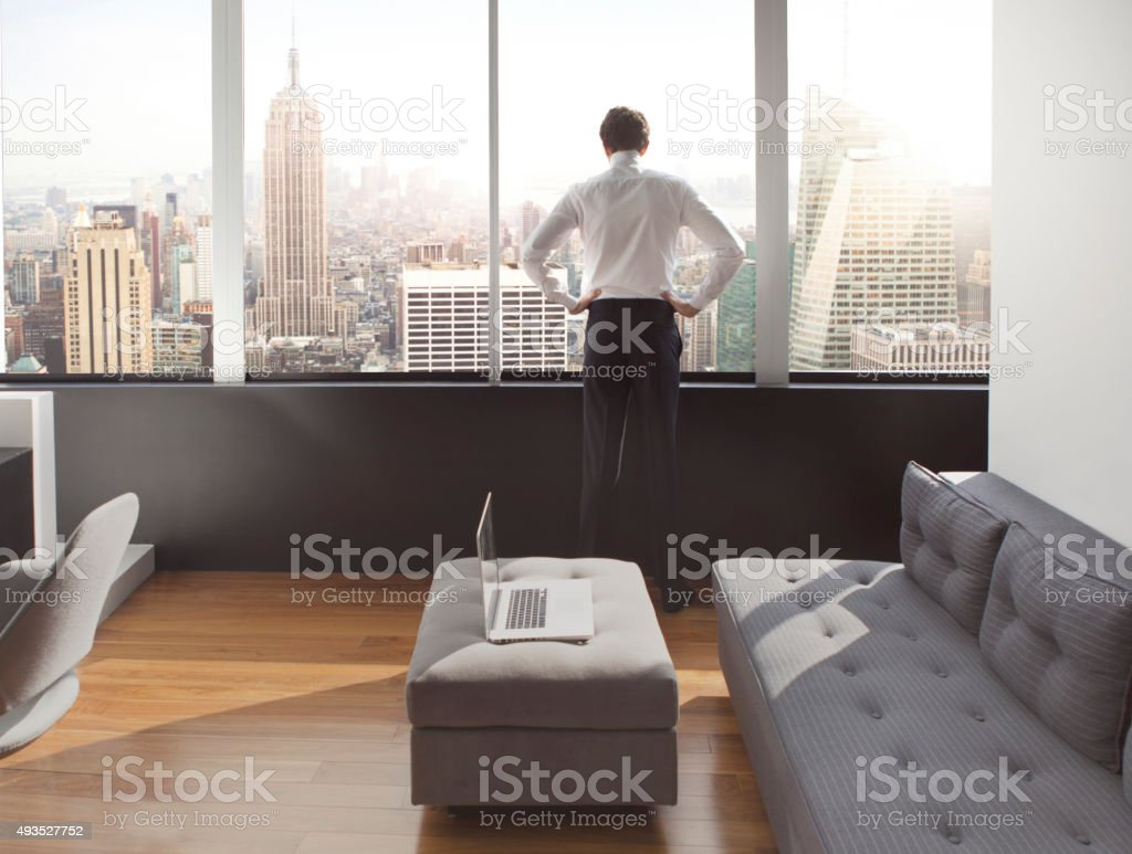 Young man looking out at city skyline stock photo