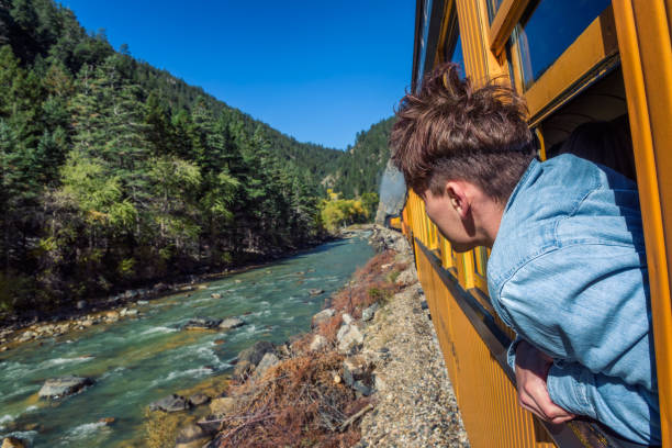 Young man looking out of train window Young man looking out of train window on the historic steam engine train travelling from Durango to Silverton along the Animas River in Colorado, USA. animas river stock pictures, royalty-free photos & images